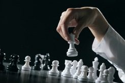Female hand moving the queen in a chess game.